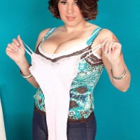 Thick dark haired solo girl Elaina Gregory uncovering titties in jeans and high-heels