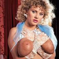 Curly golden-haired Suzanne Brecht reveals her monster-sized boobs in lace lingerie and gloves
