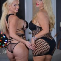 Curvy older blond Karen Fisher and her lezzy gf break out a sex toy on a bed