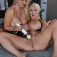 Curvy older ash-blonde Karen Fisher and her sapphic gf break out a sex toy on a bed
