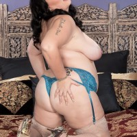 Brown-haired BIG SEXY LADY Charlotte Angel sets her big tits free of lingerie on top of a bed