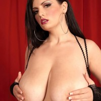 Dark haired solo chick Arianna Sinn slurps a nipple after loosing her humungous tits