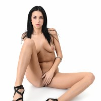 Black-haired babe Foxxi Ebony strips to her high heels before toying her shaven coochie