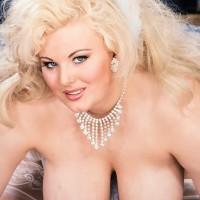 Notorious platinum-blonde X-rated film starlet Toni Evans lets her big boobs fall loose in over the knee nylons