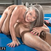 Fit elderly woman Leilani Lei deep-throats her private trainer's black cock on a wrestling pad