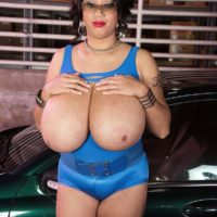 Glasses clad black-haired solo chick Roxi Crimson revealing humungous tits beside car
