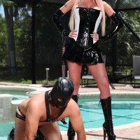 tempting blond Domme Alexia Jordon straddles a hooded masculine sub in spandex by the pool