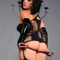 Fabulous brown-haired Belle Noir spanks her phat caboose with a whip in a revealing ebony sundress