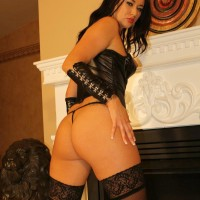 Cool dark haired Dominatrix Ashley plays with her erect nips in leather and stockings