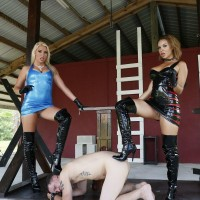 Gorgeous mistresses Cherry Morgan and Kylie Rogue use a masculine submissive as bench to sit upon