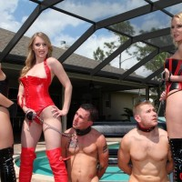 Seductive females in latex garment and hip high boots manhandle collared male subs by a pool