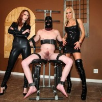 Latex clad Dommes Zoey and Kendra jerking off restrained and masked masculine submissive