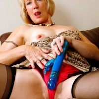 Mature golden-haired broad hikes up her dress in order to toy her snatch in ebony pantyhose