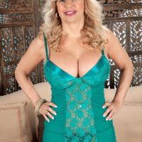 Mature ash-blonde dame Miss Deb looses her massive boobies from her lingerie on a sofa