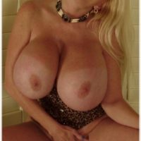 Aged sandy-haired dame Kayla Kleevage sets her enhanced boobies and thicket free on a couch