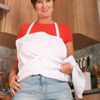 Mature housewife with short crimson hair looses her enormous naturals for her first nude poses