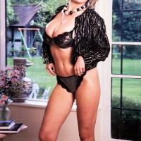 Mature MILF Debbie Q proudly displays her superb juggs in black bloomers