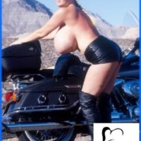 Mature model Kayla Kleevage puts her big boobs on demonstrate in leather by a motorcycle