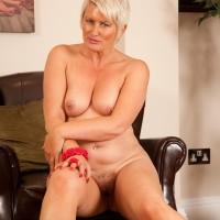 Elderly platinum yellow-haired releases her diminutive breasts as she strips to high-heels on a leather chair