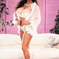 Mature X-rated film star Big-titted BriAnna sets her large breasts free in a g-string and high heeled shoes