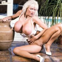 Aged XXX film starlet Platinum Peaks unleashes large tits from bra in lace undies and stilettos