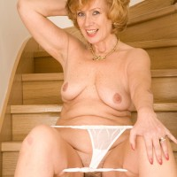 Experienced redhead doffs a sundress and pretties to pose entirely naked on wooden stairs