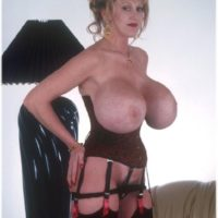 Mature solo model Kayla Kleevage demonstrates her giant fake boobs in a midbody cincher