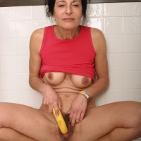 Mature lady strips naked in the kitchen before taking a banana to her unshaven beaver