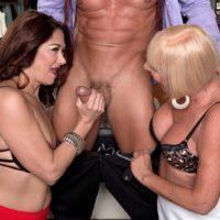 Elder girls Renee black and Scarlet Andrews take turns slurping a firm penis