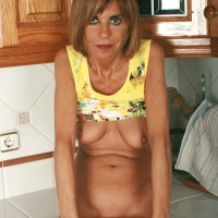 Middle aged housewife removes denim jeans and undies to model naked in kitchen