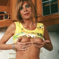 Middle senior housewife takes off jeans and panties to model nude in kitchen