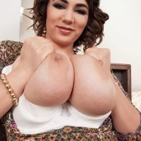 MILF solo model Alexya baring large boobies from boulder-holder in tan stockings and heels