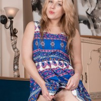 All natural golden-haired Aston Wildegets nude on a chesterfield before spreading her furry gash
