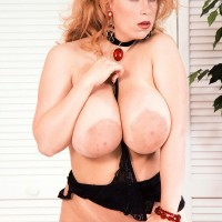 Natural ginger-haired Tabatha Towers plays with her immense tits in a choker and hosiery