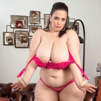 Plus-sized solo female Mia Hotty stripping down to rosy bra and panty set on chesterfield