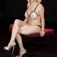 Senior platinum-blonde Cammille Austin wears nipple forceps while strutting semi-transparent lingerie