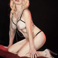 Senior platinum-blonde Cammille Austin wears nipple forceps while strutting semi-transparent lingerie