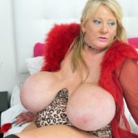 Mature sandy-haired Kayla Kleevage gobbles a nipple while playing with her enhanced tits