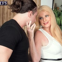 Mature sandy-haired dame Charlie has her gigantic boobs unsheathed by junior stud in a crimson miniskirt