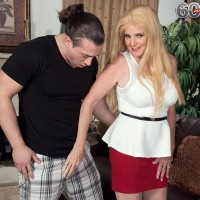Mature light-haired broad Charlie has her immense funbags uncovered by junior dude in a red microskirt