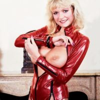 Aged light-haired MILF Debbie Ashby extracts her humungous breasts from a latex jacket in hose