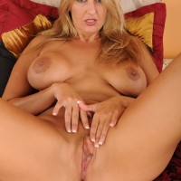 Senior light-haired MILF unsheathes her humungous titties preceding to slipping off her thong and masturbating