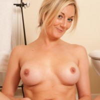 Senior sandy-haired solo model stripping nude to pose naked in the washroom