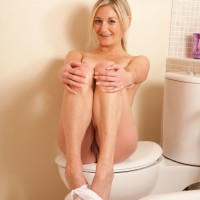 Senior light-haired solo model stripping nude to pose naked in the bathroom