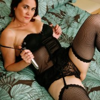 Old dark haired woman in ebony stockings plunging sex toy into trimmed beaver in high heeled shoes