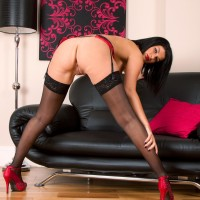 Elder black-haired model revealing ideal boobies in wondrous black hose and high heels
