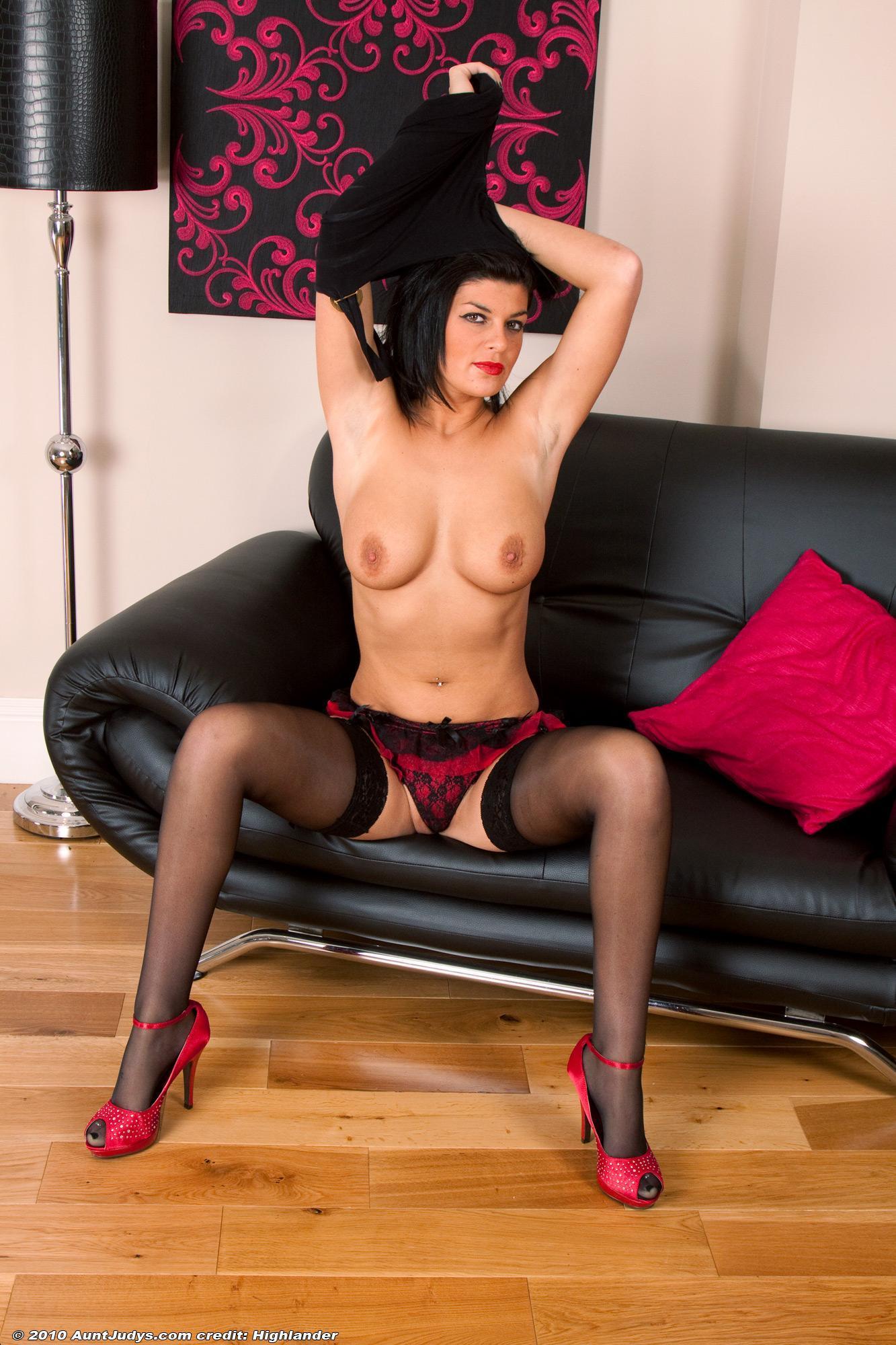 Elder black-haired model revealing ideal boobies in wondrous black hose and high heels