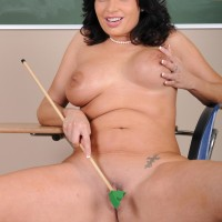 Mature brown-haired educator baring huge boobies and shaven snatch in stilettos
