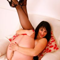 Aged brown-haired solo model revealing massive boobs and plus sized ass in black nylons and high-heeled shoes