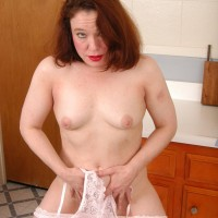 Senior redhead girlfriend discarding translucent attire and lingerie to pose naked in kitchen